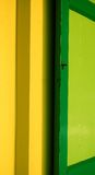 Green shutter on yellow wall. Vibrant green shutter with key on yellow wall Royalty Free Stock Images