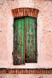 Green shuttered window. Exterior details of green weathered shutters on building window Stock Photo