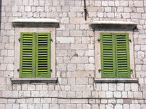 Green shutters. Two windows with green shutters on the facade of the ancient stone building stock photos