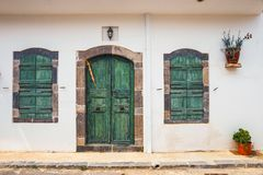 Green shutters and doors on a white wall. Close up Royalty Free Stock Image