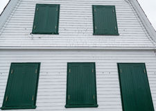 Green Shutters on Old White Wood Building Stock Image