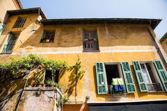 Green Shutters on Open Windows of Yellow Plaster Building Royalty Free Stock Image