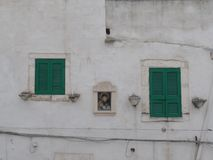 Green shutters of a white washed house in Ostuni, Puglia, Southern Italy royalty free stock photography