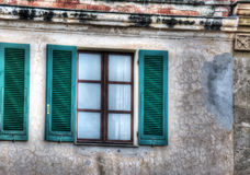 Green shutters in a rustic wall Stock Image