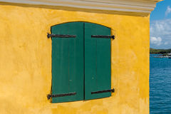 Green shutters on yellow stucco wall. View of the blue ocean in the background Royalty Free Stock Photos