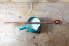 Green side handle bowl pitcher of almond milk, centered, very long wooden spoon with single almond balanced on top. Horizontal aspect Royalty Free Stock Photo