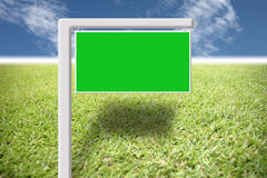 Green sign on the lawn and blue sky. Royalty Free Stock Image