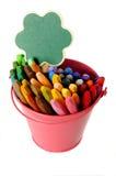 Green sign on metal bucket full of crayon Stock Image