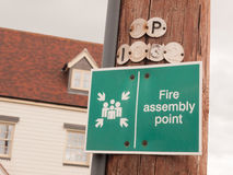A green sign outside on a wooden pole saying fire assembly point Royalty Free Stock Images
