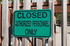 Green sign reading Closed Authorized Personnel Only posted on a fence. Post royalty free stock photo