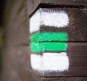 Green sign on wooden wall, czech tourism. Hiking green and white arrow sign on wooden wall corner, typical for czech tourism, providing guidence, touristic Stock Images