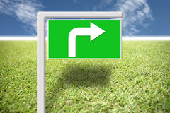 Green signs with arrows on the grass and blue sky. Stock Images