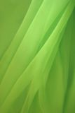 Green silk. Lying chaotic folds lying on a horizontal surface Stock Image