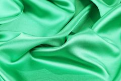Green silk background soft folds and highlights. Stock Photo