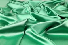 Green silk. Green sik background with some soft folds and highlights royalty free stock image