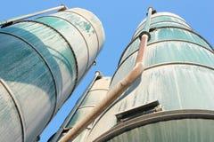 Green silos. Cement silos over a blue sky Stock Photo