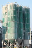 Green silos. Cement silos over a blue sky Royalty Free Stock Photography