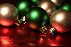 Green and Silver Balls. Green and silver Christmas balls/baubles resting on red metallic wrapping paper Royalty Free Stock Photo