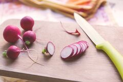 Green and Silver Kitchen Knife Beside Pink Onions Royalty Free Stock Photography
