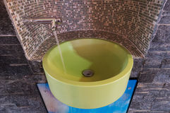 Green sink or washbowl with water tap with mosaic. Green washbowl with water tap niched with mosaic tiles and flowing water Royalty Free Stock Photography