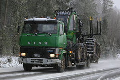 Green SISU Truck Hauls John Deere Forwarder in Winter Stock Image