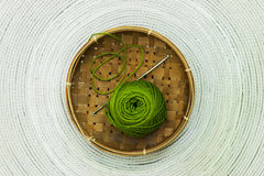 Green skein of wool in brown basket Stock Image