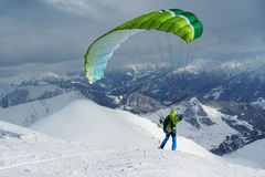 Green skier starts with a paraglider in  highlands Royalty Free Stock Photos