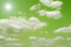 Green Skies. Interesting green sky gradient background and many white clouds and beaming sun royalty free stock images