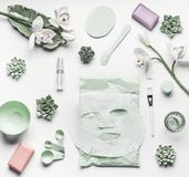 Green skin care cosmetic setting with orchid flowers, accessories and facial calming sheet mask on white. Background, top view, frame, flat lay. Beauty concept royalty free stock photo