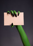 Green skin hand with sharp nails holding empty piece of cardboar Stock Images