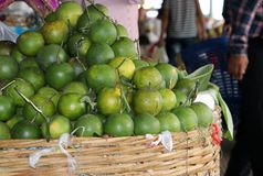 Green skin of orange placed in a bamboo basket for sell. royalty free stock images