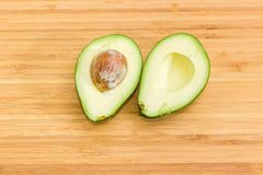 Green avocado cut in half on bamboo cutting board stock photo