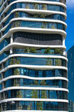 Green skyscraper building with curvy organic forms and plants gr Royalty Free Stock Image