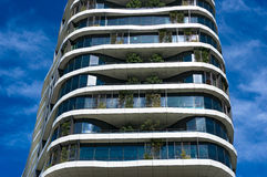 Green skyscraper building with curvy organic forms and plants gr Stock Image