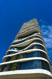 Green skyscraper building with curvy organic forms and plants gr Stock Photo