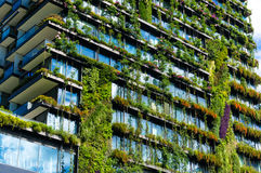 Green skyscraper building with plants on the facade. Green skyscraper building with plants growing on the facade. Ecology and green living in city, urban Royalty Free Stock Photo
