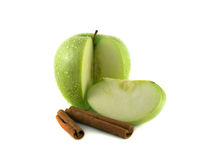 Green sliced apple with cinnamon pods. (white background). Fresh diet fruit (water drops). Healthy fruit with vitamins Stock Image
