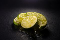 Green sliced limes with water drops on black background, horizontal shot Stock Images