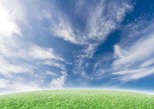 Green slope with idyllic blue sky. Beautiful nature background with green grass and blue vivid sky with clouds royalty free stock images