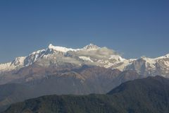 A green slope of a mountain against the backdrop of clouds and the Annapurna snow ridge under a clear blue sky. Green slope of a mountain against the backdrop of royalty free stock image