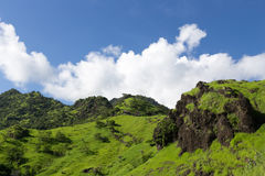 Green slope of the volcano on a background of blue sky with clouds Royalty Free Stock Photography