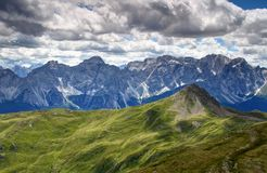 Green slopes of Carnic Alps and cliffs of Sexten Dolomites Royalty Free Stock Image