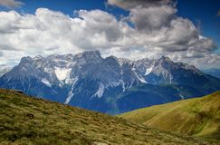 Grassy Carnic Alps and jagged Sexten Dolomites, Italy. Green slopes of Carnic Alps main ridge and jagged Dreischusterspitze / Punta dei Tre Scarperi and Haunold Stock Photo