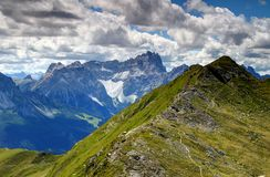 Grassy Carnic Alps with jagged peaks of Sexten Dolomites, Italy. Green slopes of Carnic Alps main ridge with jagged Dreischusterspitze / Punta dei Tre Scarperi Royalty Free Stock Photos