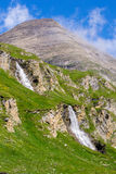 Green slopes with two waterfalls and a mountain peak Royalty Free Stock Image