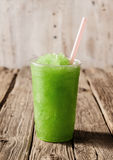 Green Slushie Drink in Plastic Cup with Straw. Close Up Still Life of Plastic Cup Filled with Refreshing Frozen Green Slush Drink and Served on Rustic Wooden Royalty Free Stock Photography
