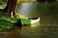 Green Small Boat. A small fishing boat at lake side Stock Photos