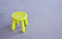 Green small chair on the gray floor. Green small chair on the gray background Royalty Free Stock Images