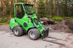 Green small forklift stands on a logging area Stock Image