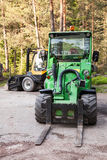 Green small forklift stands on a logging area Stock Photo